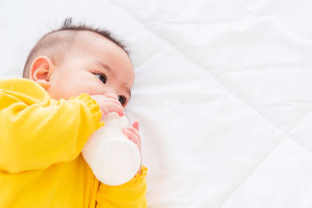 Asian beautiful little baby girl wearing a yellow dress eat milk sleeping feeding lying on the white bed, infant holding a bottle of milk, baby food concept