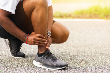 Close up Asian young sport runner black man wear watch hands joint hold leg pain because of twisted ankle broken while running at the outdoor street health park, healthy exercise Injury from workout