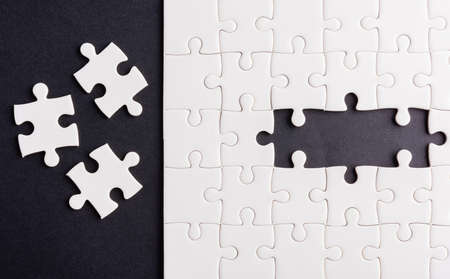 Top view flat lay of paper plain white jigsaw puzzle game texture last pieces for solve and place, studio shot on a black background, quiz calculation concept