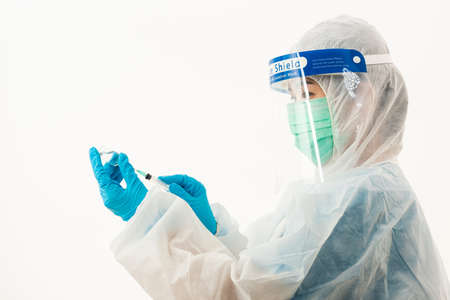 Woman medical scientist in PPE uniform wearing a face mask protective and plastic face shield holding for vaccine and syringe quarantine Coronavirus outbreak (COVID-19) isolated on white background Stock Photo