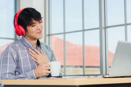 Asian young businessman happiness with red headphones sitting on desk workplace home office with a laptop computer, confident handsome man lifestyle smile relax holding a coffee cup, listens to music Archivio Fotografico