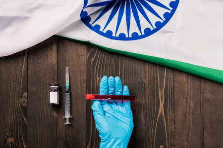 Hands of a doctor wearing gloves holding blood test tube coronavirus (COVID-19) virus in the laboratory with the flag India on wooden background, Indian Vaccination 写真素材