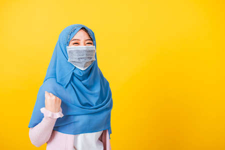 Asian Muslim Arab, Portrait of happy beautiful young woman Islam wear veil hijab and face mask protect raise hands glad excited cheerful after recovering from illness coronavirus isolated yellow 写真素材
