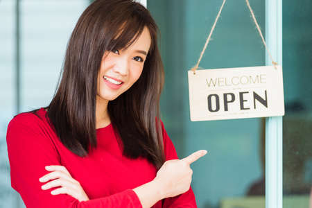 New normal, Asian young woman glad and smiling point finger to notice sign wood board label