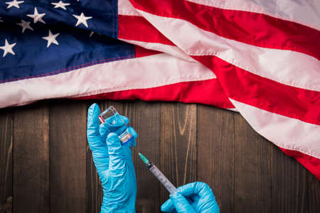 Hands of a doctor wearing gloves holding coronavirus (COVID-19) vial vaccine and syringe with flag United States of America on wood background, USA Vaccination