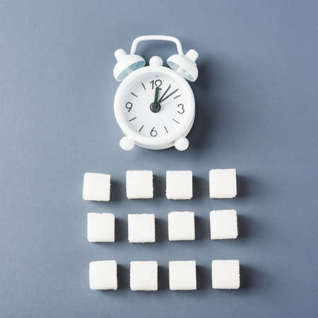 White sugar cube sweet food ingredient geometry pattern and alarm clock, studio shot isolated on a gray background, Minimal health high blood risk of diabetes and calorie intake concept Stock fotó