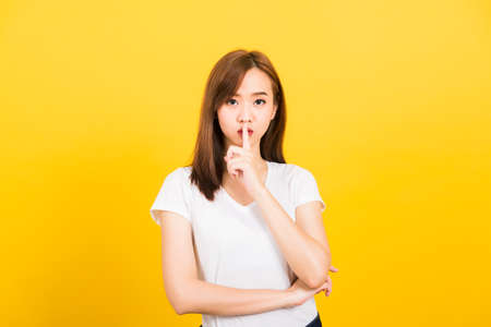 Asian happy portrait beautiful cute young woman teen smile standing wear t-shirt making finger on lips silent quiet gesture looking to camera isolated, studio shot on yellow background with copy space 免版税图像