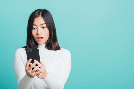 Portrait female anxious scared on the phone seeing bad news, Young beautiful Asian woman surprised shocked with mobile phone close mouth with palm, studio shot isolated on a blue background Stock fotó