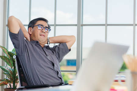 Asian hard senior businessman working with laptop computer has a problem with neck pain. Old man feeling pain after sitting at desk long time, Healthcare and medicine office syndrome concept Stock Photo