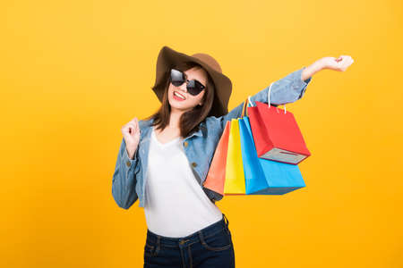 Asian happy portrait beautiful cute young woman teen smiling standing with sunglasses excited holding shopping bags multi color looking camera isolated, studio shot yellow background with copy space