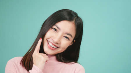 Portrait young Asian beautiful woman smiling wear silicone orthodontic retainers on teeth isolated on blue background, Teeth retaining tools after removable braces. Dental hygiene and health concept