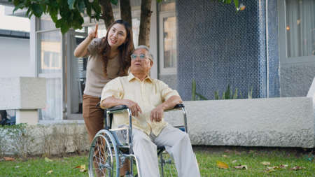 Disabled senior man on wheelchair with daughter, Happy Asian generation family having fun together outdoors backyard, Care helper young woman walking an elderly man smiling and laughed Stock fotó