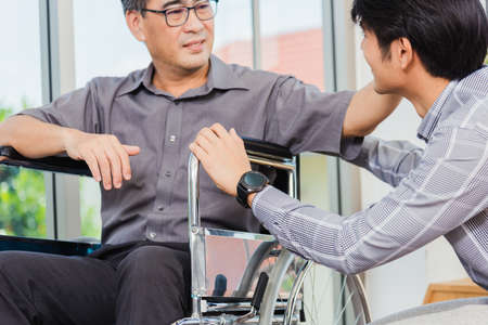 Asian senior disabled businessman in wheelchair discuss interacting together with the team in the office. The old man in a wheelchair and his young son talking to and comforting bound father