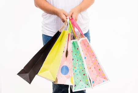 Happy woman hand holding shopping bags multicolor, young female hold many packets within arms isolated on white background, Black friday sale concept