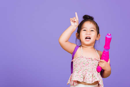 Happy Asian little girl holding plastic water gun, Thai child funny hold toy water pistol and smile, studio shot isolated on purple background, Thailand Songkran festival day national culture concept