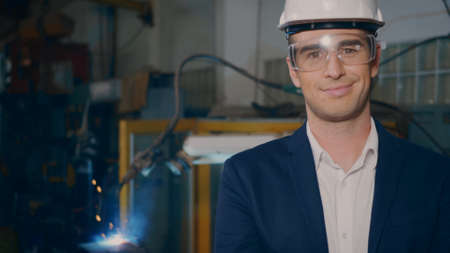 Professional confident engineer businessman in suits safety hats, goggles smile look at camera stand in heavy industrial facility manufacturing with steel welding from with fire spark