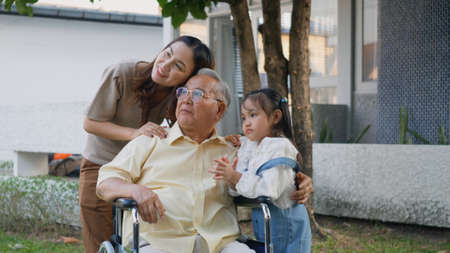 Disabled senior grandpa on wheelchair with grandchild and mother in park, Happy Asian three generation family having fun together outdoors backyard, Grandpa and little child smiling and laughed Stock fotó