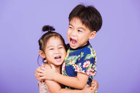 Asian Two happy funny little cute kids stand together in studio shot isolated on purple background, happy family brother and sister hugging each other feeling love (4 years old boy, 2 years old girl) Archivio Fotografico