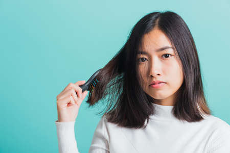 Young beautiful Asian woman upset with a comb and problem hair, Portrait female shocked suffering from hair loss problem, studio shot isolated on a blue background, medicine health concept Stock fotó