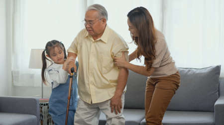 Asian family, Daughter and granddaughter take care support grandfather who is suffering from knee pain Got walking outside to take a walk And grandpa with a stick, elderly health care concept