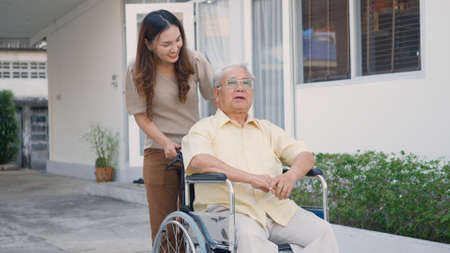 Disabled senior man on wheelchair with daughter, Happy Asian generation family having fun together outdoors backyard, Care helper young woman walking an elderly man smiling and laughed