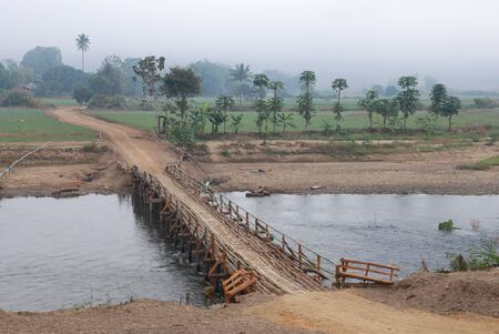 A wooden  bridge over the river and Dirt Road