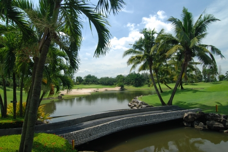 Golf course in Thailand,stone bridge across the water to green photo