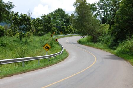 Asphalt road sharp S-Curve Road  along with tropical forest photo