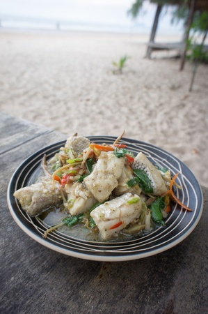 Fried herbal vegetables with fish at the beach