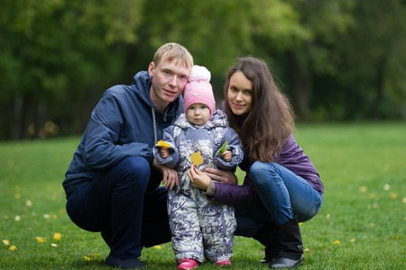 autumn young: Happy family: Father, Mother and child - little girl in autumn park: dad, mammy baby posing outdoor, telephoto shot Stock Photo