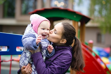 mammy: Happy family: Mother and child - little girl walking in autumn park: baby and mammy posing at playground, close up, telephoto shot Stock Photo