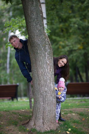 mammy: Happy family: Father, Mother and child - little girl walking in autumn park: mammy playing the airplane, telephoto shot