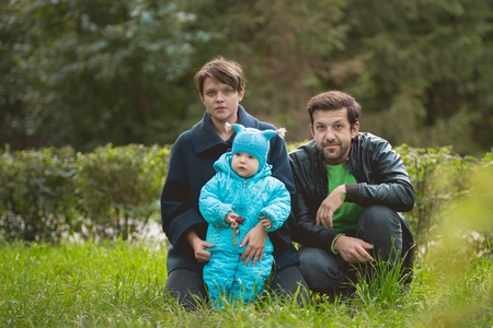 Family walking in the autumn park - Father, mother and little son posing on the grass, telephoto Stock Photo