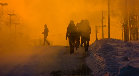 evaporation: People going on the street in foggy evaporation at sunset, background, frozen dusk Stock Photo