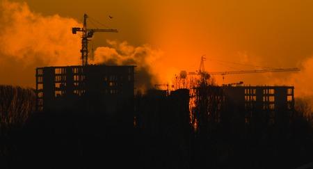 evaporacion: Casa en construcción en la evaporación de niebla en la puesta del sol, fondo, oscuridad congelado