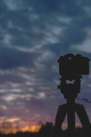 photgraphy: Camera standing on tripod at sunset sky, landscape, spring in Ural, close up Stock Photo
