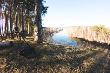 photgraphy: Camera standing on tripod at morning on forest river landscape, spring in Ural, panoramic, wide angle