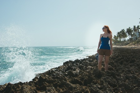 medium shot: Young woman in in shorts and t-shirt standing on rocks and looking to a sea, medium shot Stock Photo