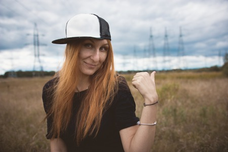 Young energy happy woman in hip-hop cap shows power pylons on yellow field, close up, cloudy autumn