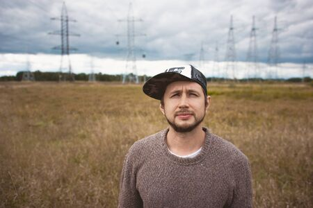 forties: Courageous young man in cap on meadow, power pylons at background, cloudy autumn