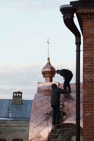 KAZAN, RUSSIA, 19 NOVEMBER 2016, two workers Roofer repairing roof of ortodox Old believers  Church in winter cold day, horizontal Editorial
