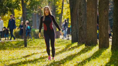 limbering: Sexy Attractive female blonde bikini-fitness model stretching in the autumn park on ground covered yellow leaves - stretching arms, telephoto