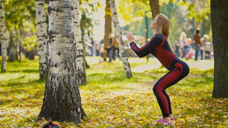 limbering: Sexy Attractive female blonde bikini-fitness model stretching in the autumn park on ground covered yellow leaves - sports squats, telephoto Stock Photo