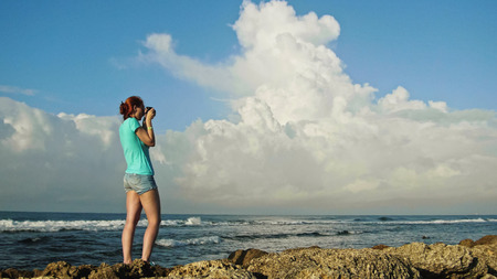 Young woman with red hair in glasses photographs sea standing on the rocks , beach of Dominican Republic, wide angle, Caribbean sea
