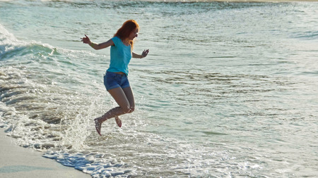 Young woman with long red hair play with waves running, feeling the sea, seascape beach of Dominican Republic, Caribbean sea Stock Photo