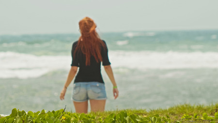 Young woman with long red hair on caribbean beach, Dominican Republic, rear view, telephoto