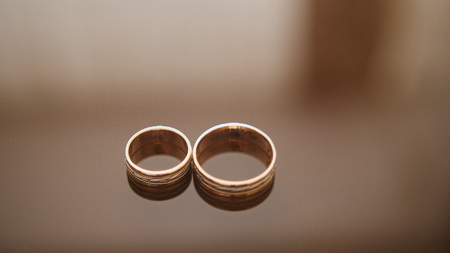 Golden wedding rings on mirror glasses table - one lies near another, macro, close up Stock Photo