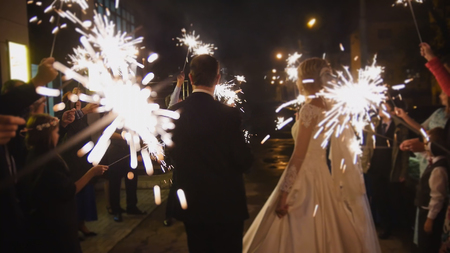 Sparkler in hands on a wedding - bride, groom and guests holding lights in hands, horizontal Banque d'images