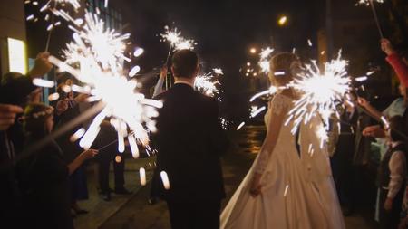 Sparkler in hands on a wedding - bride, groom and guests holding lights in hands, horizontal Standard-Bild