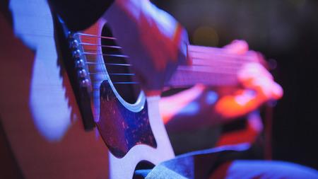 -夜のクラブでミュージシャン ギタリスト ブルース アコースティック ギターを果たしている、非常にクローズ アップ、望遠